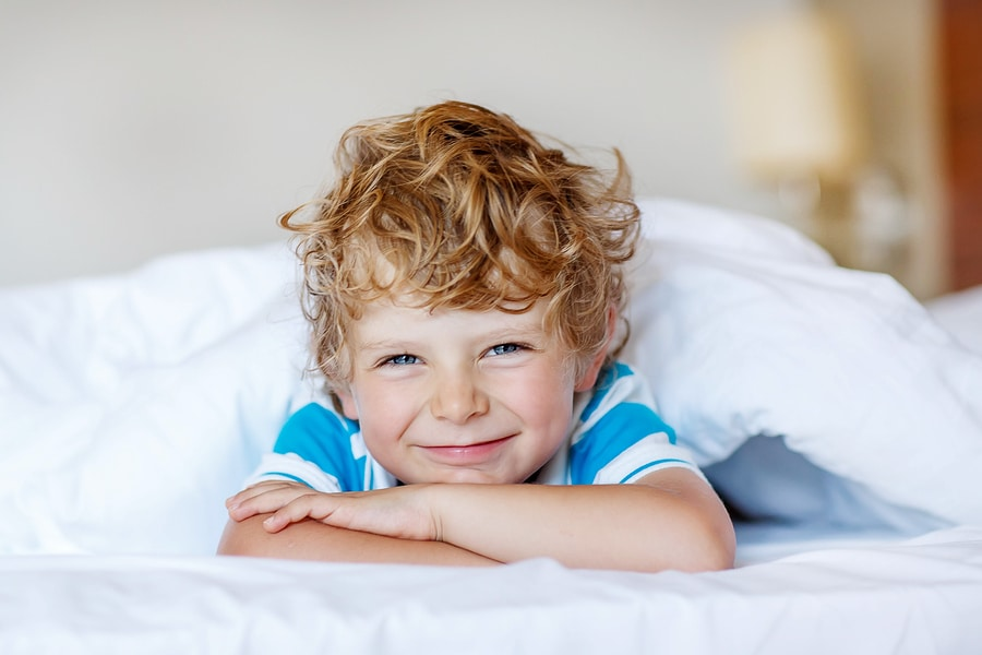 Beautiful happy kid boy after sleeping in his white bed. Little happy child smiling and laughing indoors.