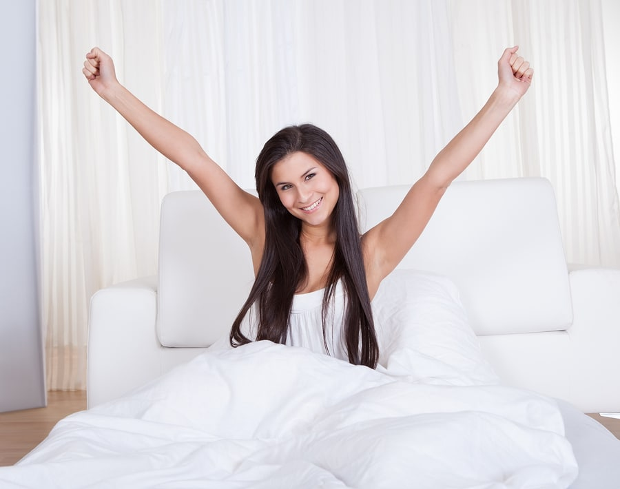 Refreshed young woman rejoicing in bed with her arms outstretched above her head rejuvenated by a good nights sleep - Best down alternative comforter, best down alternative comforter