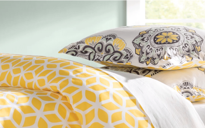beautiful yellow and white with brownish color of the bed cover, pillows blanket with floral design or abstract