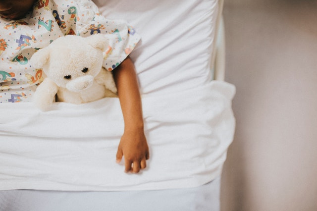 a girl with a teddy bear toy lying on bed with white bedsheet