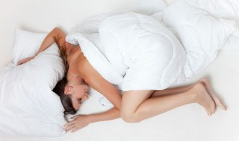 Woman sleeping on a white duvet