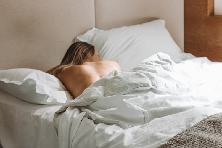 woman lying on bed during daytime