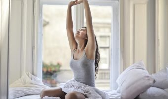 woman on bed stretching for mattress protector article