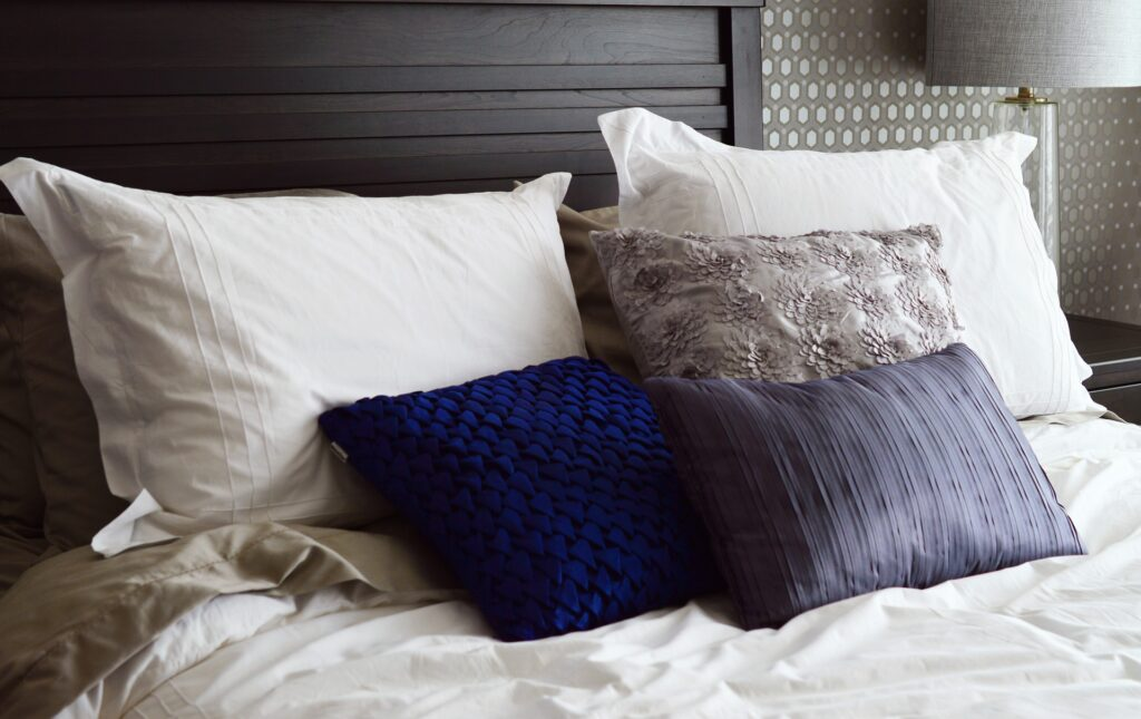 Blue, silver, and white pillows on a bed