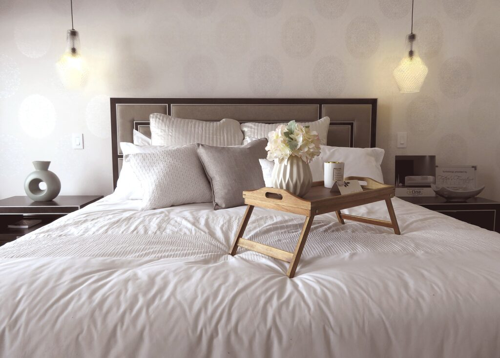 A tray sitting on a bed with a eiderdown comforter