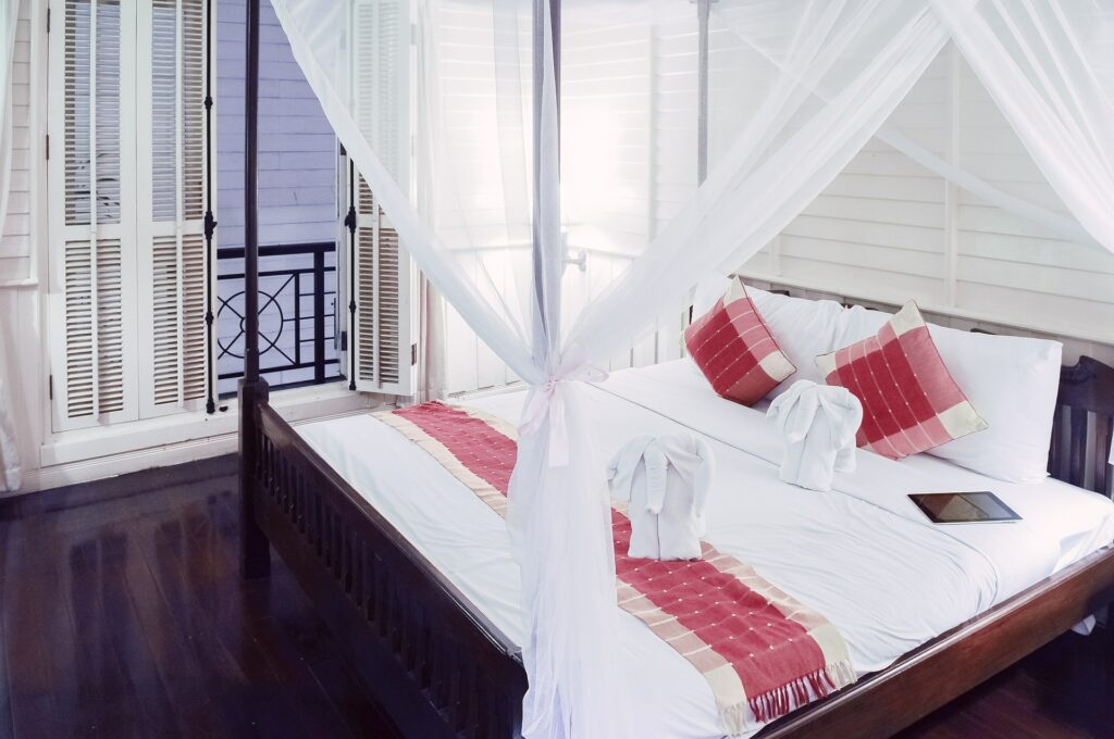 A canopy bed with an eiderdown comforter