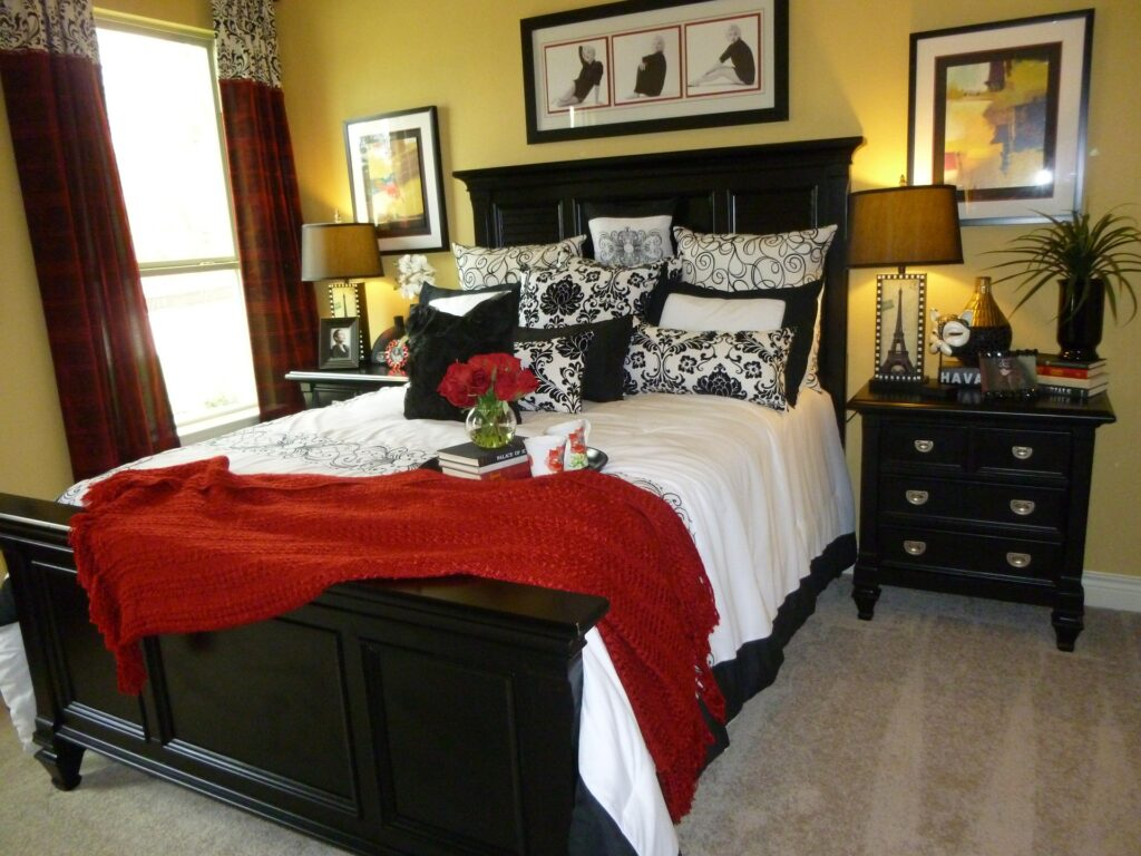 A bed with fancy red pillows