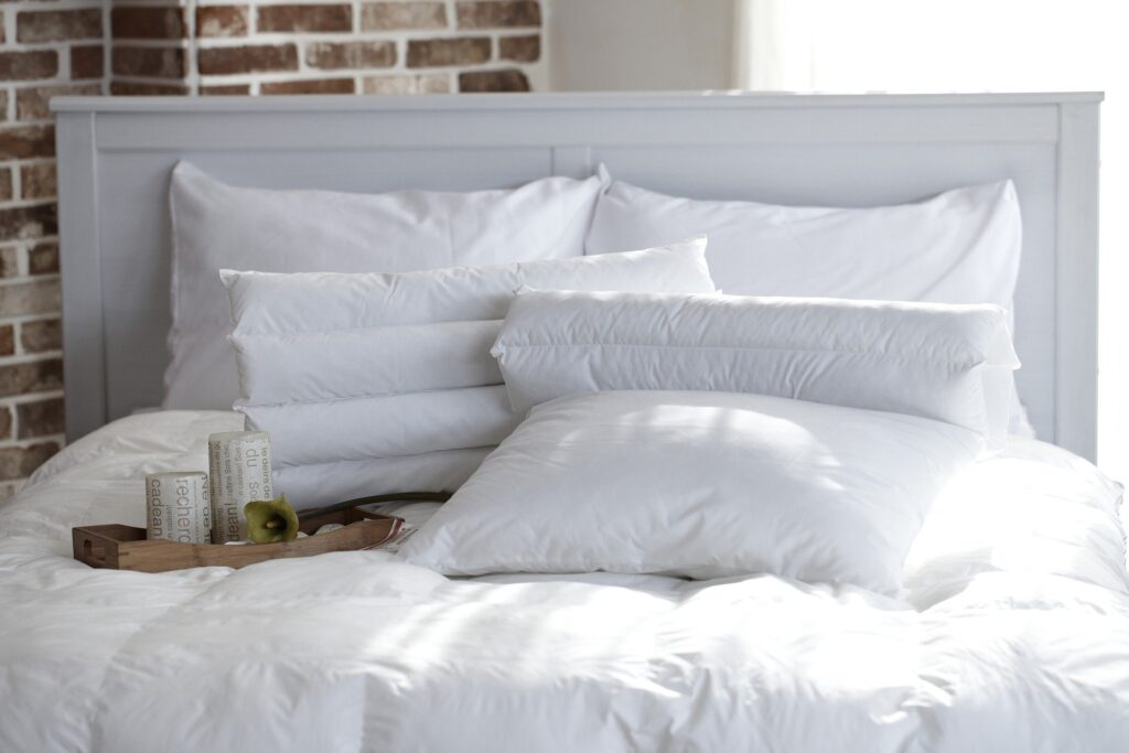 Pillows and a tray sitting on a bed but can you wash feather pillows