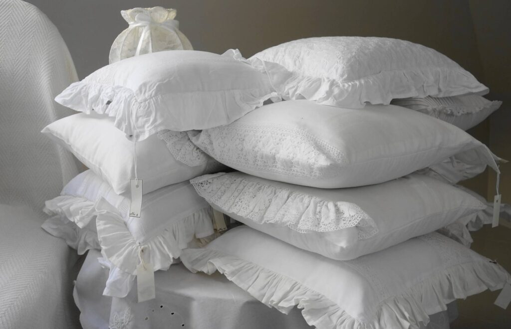 Decorative pillows stacked on a bedside table